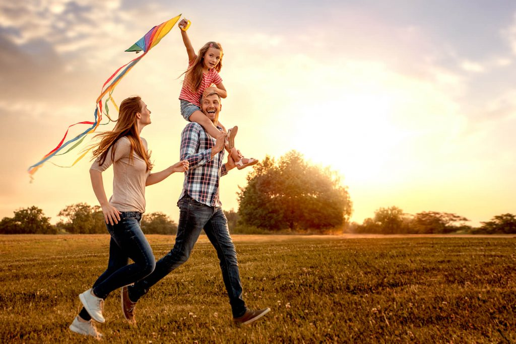 Image of family running with a kite at sundown