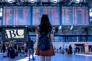 Girl looking at departure board at airport